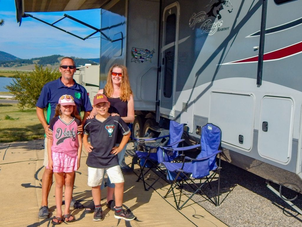 The Foley family stands in front of their RV
